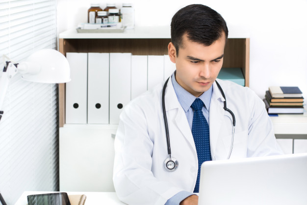handsome young doctor working laptop computer searching information online 8087 2760